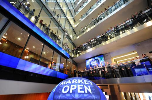 People at the London Stock Exchange watch the new opening bell. The inaugural event saw a timer on a giant globe mark the 8am opening, before Chancellor George Osborne triggered trade by 'unlocking' the market with a plastic key. The ceremony will become a regular event with companies and celebrities expected to turn the key on important occasions, such as a stock market flotation. Photo: PA
