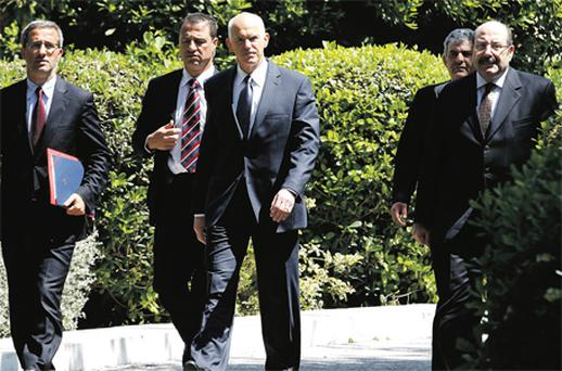 Greece's Prime Minister George Papandreou (centre) leaves the presidential mansion after a meeting with President Karolos Papoulias in Athens yesterday. Greece denied reports it was discussing a new €60bn bailout with international lenders and its borrowing costs rose amid fears it may have to restructure its debt without further EU help