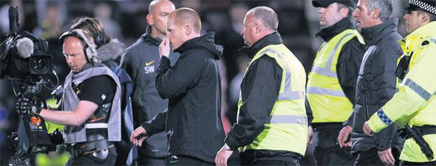 Neil Lennon leaves the Tynecastle pitch at the end of Celtic's game against Hearts last night having been attacked by a fan during the game.