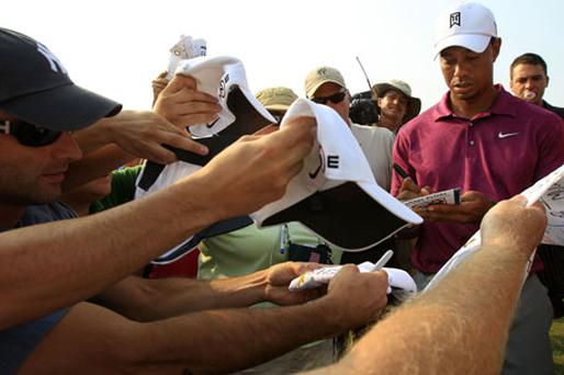 Tiger Woods signs autographs for fans during a practice round prior to the start of The Players Championships at Sawgrass. Photo: Getty Images