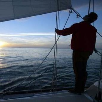 A man who sailed around the world - using his school atlas to cross the Atlantic - has returned to the UK