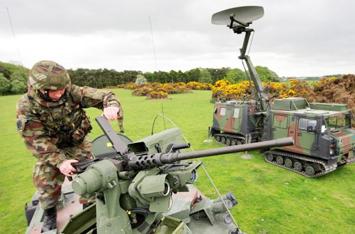LOCK AND LOAD: Irish Defence Forces gunner Robert O'Carroll checks a remote operated .50 machine gun on a light tactical armoured vehicle beside a Giraffe radar system, which will be deployed during the Queen's visit. Photo: Frank McGrath