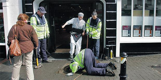 Gardai check a manhole on Main Street, Kilcullen in County Kildare yesterday in advance of the royal visit