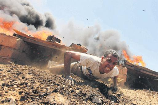 A civilian volunteer of the rebel army clears an obstacle course during training in Benghazi yesterday.