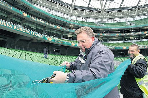 Alan Regan from Pulse Security ( right) holds security netting for Paul Barnes from the FAI Safety and Security Department to cut as they cordon off sections of the seating for the EUFA Europa League Final