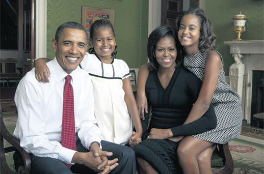 President Barack Obama, First Lady Michelle Obama, and their daughters, Malia and Sasha, sit for a family portrait in the Green Room of the White House