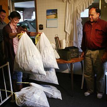 Josh and Tara Ferrin with some of the bags of money they found at their new home (AP)