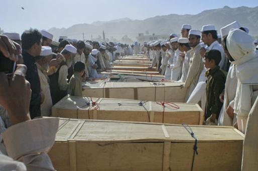 Residents of Khyber in northwest Pakistan stand over the caskets of those killed by a secondary blast at the site of a NATO tanker on Saturday. At least 16 people were killed after a bomb attack, claimed by a militant group, hit a truck carrying fuel supplies for NATO. Photo: Reuters