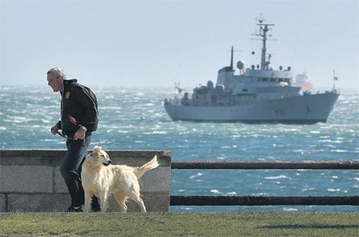 A man walks his dog near Dun Laoghaire as an Irish Naval vessel patrols in Dublin Bay