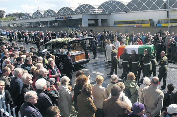 Crowds line the streets as Garret FitzGerald's coffin is loaded into a hearse for the journey to Shanganagh Cemetery