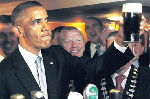 President Obama enjoys a pint in Ollie Hayes' bar yesterday