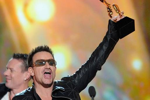 Bono clutches the award for U2's latest tour. Photo: Getty Images