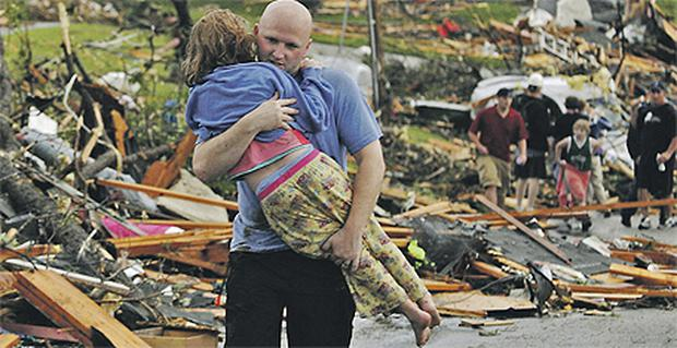 A man carries a rescued girl in the devastated city of Joplin yesterday