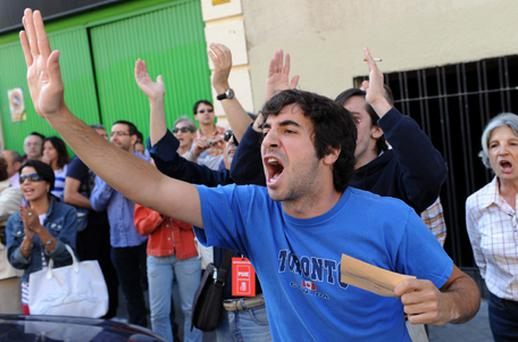 People shout slogans as Spain's Prime Minister Jose Luis Rodriguez Zapatero arrives at the Colegio Nuestra Senora del Buen Suceso to vote in Spain's regional elections on May 22 in Madrid. Despite a ban on political protests ahead of Spain's regional elections about thirty thousand demonstrators, angry with the high youth unemployment and economic policies, have gathered in the capital's central Puerta del Sol. Photo: Getty Images