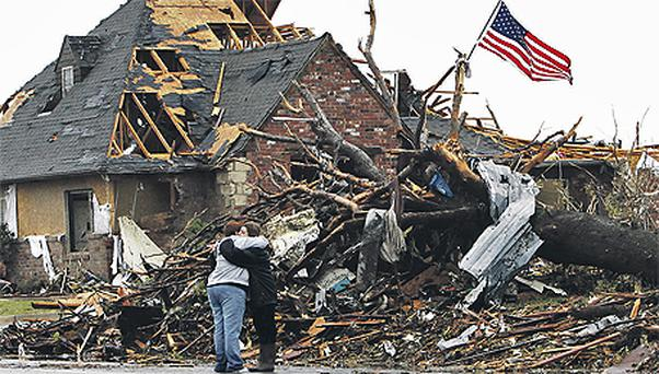Co-workers Cindy Albers, left, and Kim Hoosier outside a home destroyed in Sunday night's tornado in Joplin, Missouri