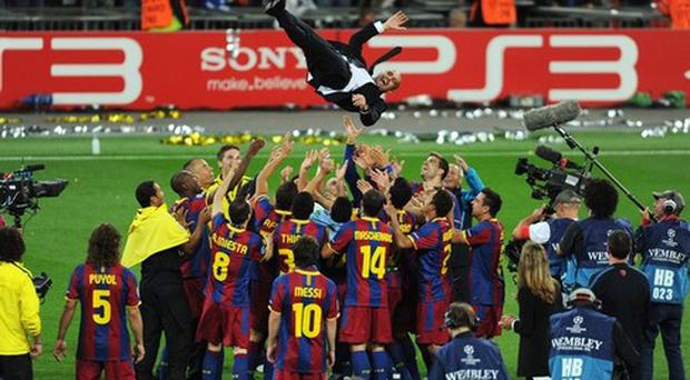 Josep Guardiola manager of FC Barcelona is thrown in the air as Barcelona celebrate victory in UEFA Champions League final between FC Barcelona and Manchester United FC at Wembley Stadium