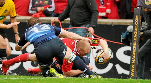 Keith Earls, Munster, goes over to score his side' s second try, despite the tackle of Brian O'Driscoll, Leinster