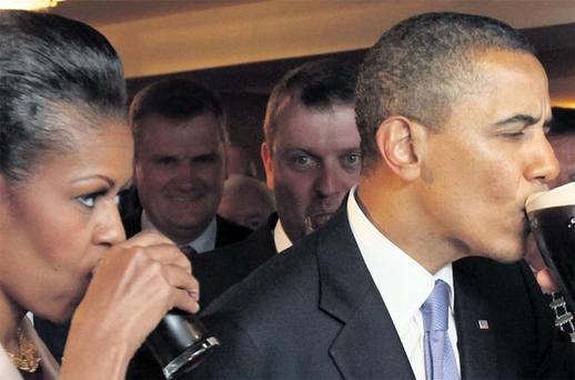 DRINKING WITH THE LOCALS: Barack and Michelle Obama downing a pint of the black stuff with the US president's Irish cousins at Ollie Hayes's bar in his ancestral village of Moneygall, Co Offaly