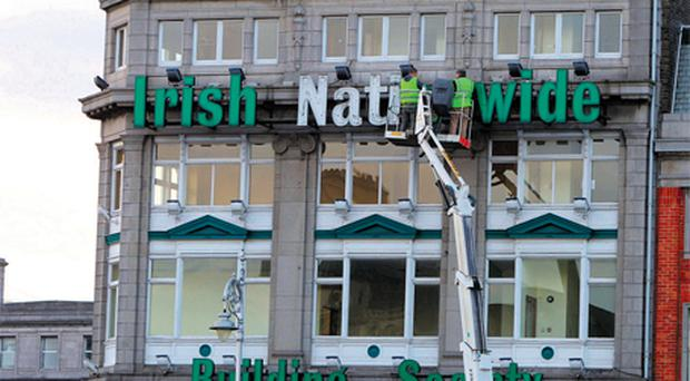 Workers from SignAge taking down the sign from Irish Nationwide Building Society on O'Connell Street, Dublin, yesterday evening. Photo: Collins