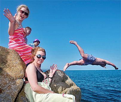 Sunseekers from Sandymount, Dublin enjoy a dip at the Forty Foot. Photo: Collins