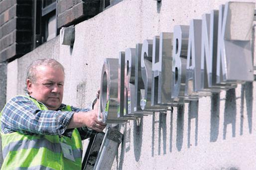 Workman Ken Glennon from 'Wayfinding' removes Anglo Irish Bank signage outside the company's headquarters on St Stephen's Green, Dublin, earlier this year