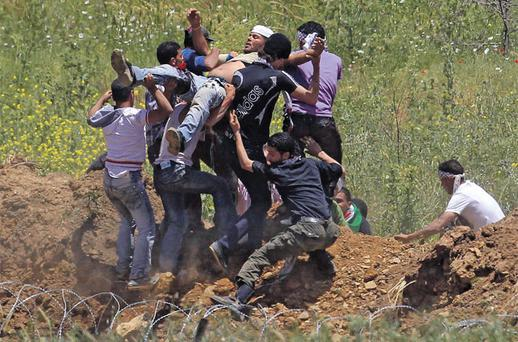 An injured protester is carried away from the Syrian-Israeli border near the Druze village of Majdal Shams in the Golan Heights yesterday