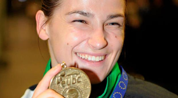 Katie Taylor has plenty of reason to smile as she shows off her gold medal to well-wishers at Dublin Airport. Photo: Ray Mc Manus / Sportsfile