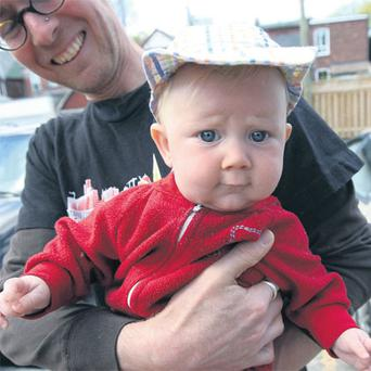 Neutral: David Stocker from Toronto holds his controversial 'genderless' child Storm