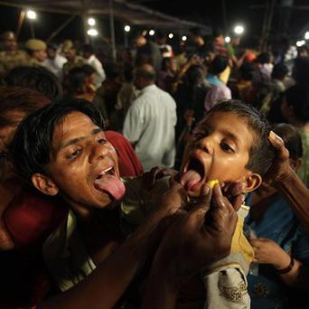 A boy in Hyderabad sticks out his tongue to swallow live sardines smeared with secret herbs, believed to be a cure for asthma (AP)