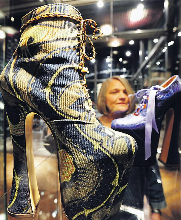 Joanna Hashagen from the Bowes Museum in Durham, England looks at the Super Elevated Ankle Boot shoe yesterday by designer Vivienne Westwood. OWEN HUMPHREYS/PA