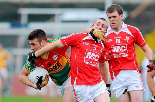 Eoghan Ruth of Carlow brushes past the challenge of Louth's Ray Finnegan during yesterday's clash at Portlaoise. Photo: Sportsfile