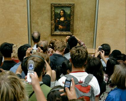 Museum mayhem: Left, crowds flock around the 'Mona Lisa' in the Louvre
