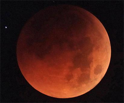 The blood red moon during a total lunar eclipse as seen from Naha, on the Japanese island of Okinawa. Photo: AP