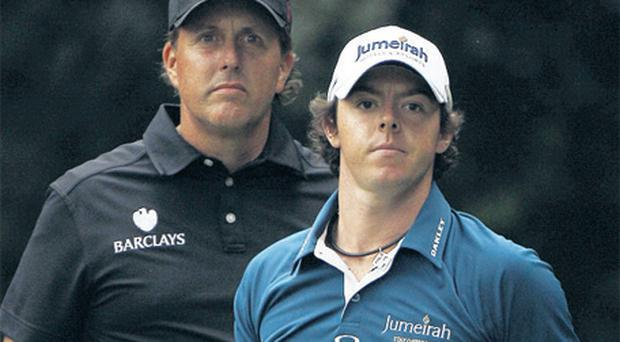 Phil Mickelson peers over Rory McIlroy's shoulder on the 14th hole during the first round of the US Open at Congressional yesterday