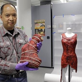 Jun Francisco, of the Rock and Roll Hall of Fame and Museum, displays a boot and dress made of meat worn by Lady Gaga