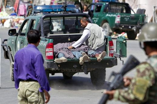 CARNAGE: Casualties are taken away after an attack by suicide bombers on a police station in Kabul yesterday. Photo: Reuters