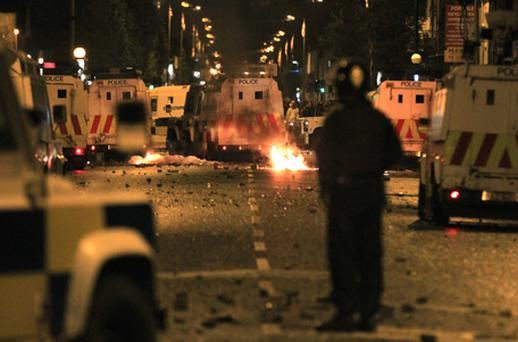 A policeman stands burning amid debris and police vehicles in east Belfast on June 21. A number of people were injured in sectarian clashes which broke out in the Short Strand area of the city. Photo: Getty Images
