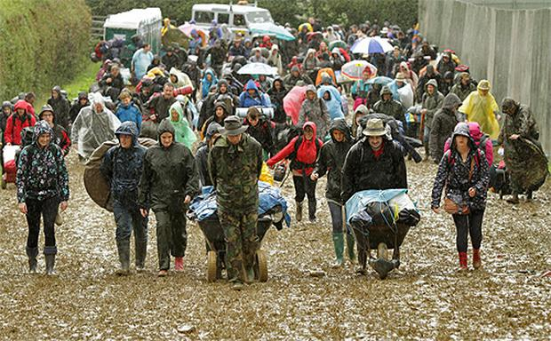 Revellers arrive to Glastonbury in the mud and the rain. Photo: PA
