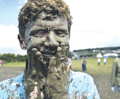 Tom Wilder from Kent, England, covered in mud at the Glastonbury festival, held on Worthy Farm, Pilton