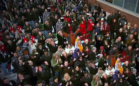 The doctored scene in which someone in a green top apparently clapping can be seen twice, as can a woman in an orange jacket raising her arms in the air