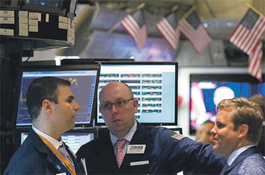 Traders work on the floor of the New York Stock Exchange in New York yesterday as US markets again saw another sell-off with the Dow paring earlier 1pc losses to close down 0.5pc and the broader S&P 500 also trimming losses to 0.28pc