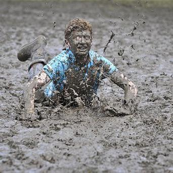 Tom Wilder, 17, from Kent, gets into the festival spirit and performs a dramatic slide in the Glastonbury Festival mud