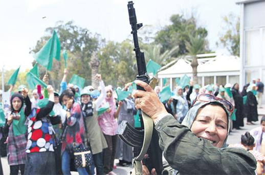 A Libyan woman fires in the air during a graduation ceremony after a weapons training course in Tripoli