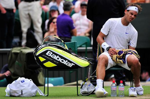 Rafael Nadal grimaces as he touches his heel as he plays against Argentina's Juan Martin Del Potro. Photo: Getty Images