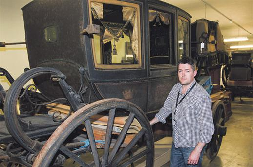 Chris Harbridge of the registration department at the National Museum, beside a Victorian coach