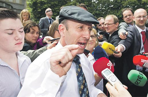 Michael Healy-Rae reads a statement to the media at Leinster House in Dublin yesterday, while his son Jackie (left) listens