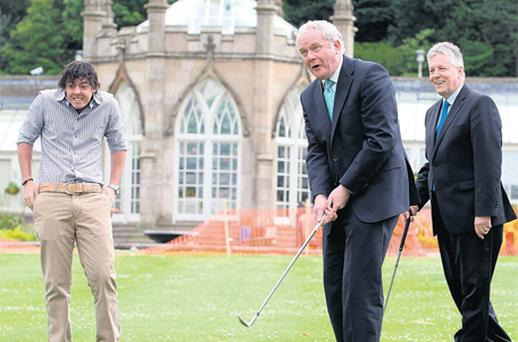 Rory McIlroy, left, winces as Martin McGuinness chips a ball toward an assistant as Peter Robinson looks on