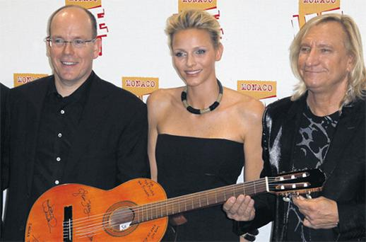 Prince Albert and his fiancee Charlene Wittstock hold a guitar offered by Joe Walsh of US band The Eagles at a concert in Monaco yesterday to mark three days of celebration in the principality for their wedding