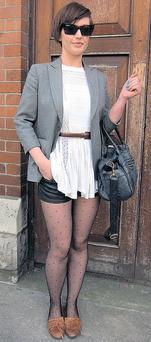 Aimee adds a pretty slant to her leather shorts and cat-eye shades with a lace drape top and sheer hosiery.