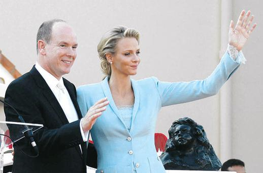 Prince Albert and Princess Charlene wave on the palace square after the service in Monaco yesterday